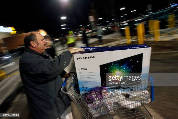 A customer leaves WalMart with his purchased items Thanksgiving day on November 28 2013 in Troy Michigan Black Friday shopping began early this year...