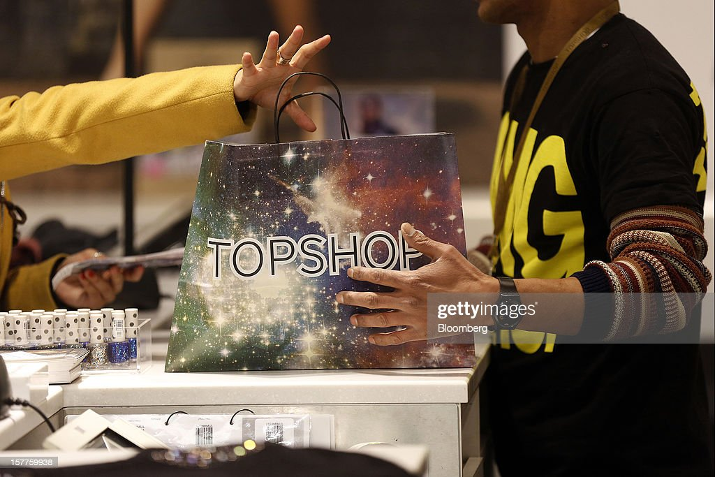A customer, left, collects a branded shopping back from a sales counter inside a Topshop store, owned by Arcadia Group Ltd., on Oxford Street in London, U.K., on Thursday, Dec. 6, 2012. Philip Green, the billionaire owner of the Arcadia fashion business, sold a 25 percent stake in the Topshop and Topman retail chains to Leonard Green & Partners LP, the co-owner of the J Crew fashion brand, in a deal valuing the businesses at 2 billion pounds ($3.2 billion). Photographer: Simon Dawson/Bloomberg via Getty Images