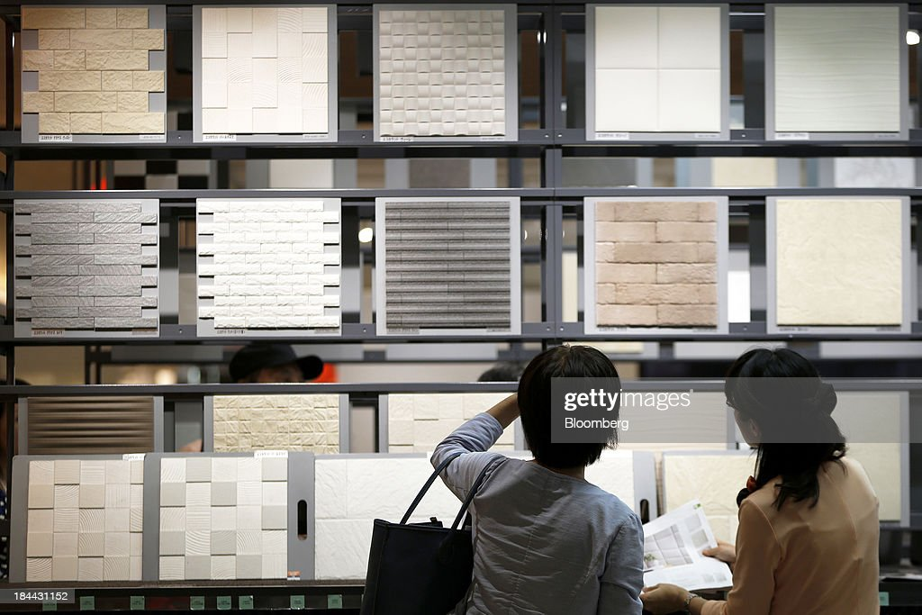 A customer, left, looks at samples of Lixil Group Corp.'s interior wall tiles with an employee at the company's showroom in Tokyo, Japan, on Friday, Oct. 11, 2013. Lixil and Development Bank of Japan agreed on Sept. 26 to buy bathroom-fixtures maker Grohe Group, valuing the German company at 3.06 billion euros ($4.1 billion). Photographer: Kiyoshi Ota/Bloomberg via Getty Images