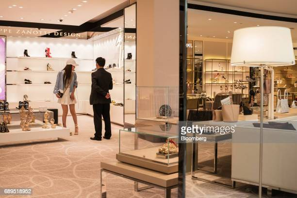 A customer left looks at shoes displayed for sale inside a store on The Boulevard at Studio City casino resort developed by Melco Crown Entertainment...
