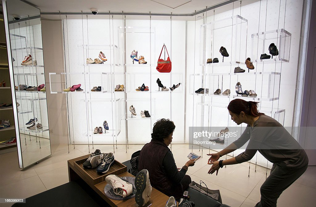 A customer, left, pays an employee for shoes inside the Geox SpA flagship store in the Central district of Hong Kong, China, on Friday, April 12, 2013.Hong Kong's economy expanded 1.4 percent in 2012 and Financial Secretary John Tsang is projecting growth of 1.5 percent to 3.5 percent this year. Photographer: Jerome Favre/Bloomberg via Getty Images