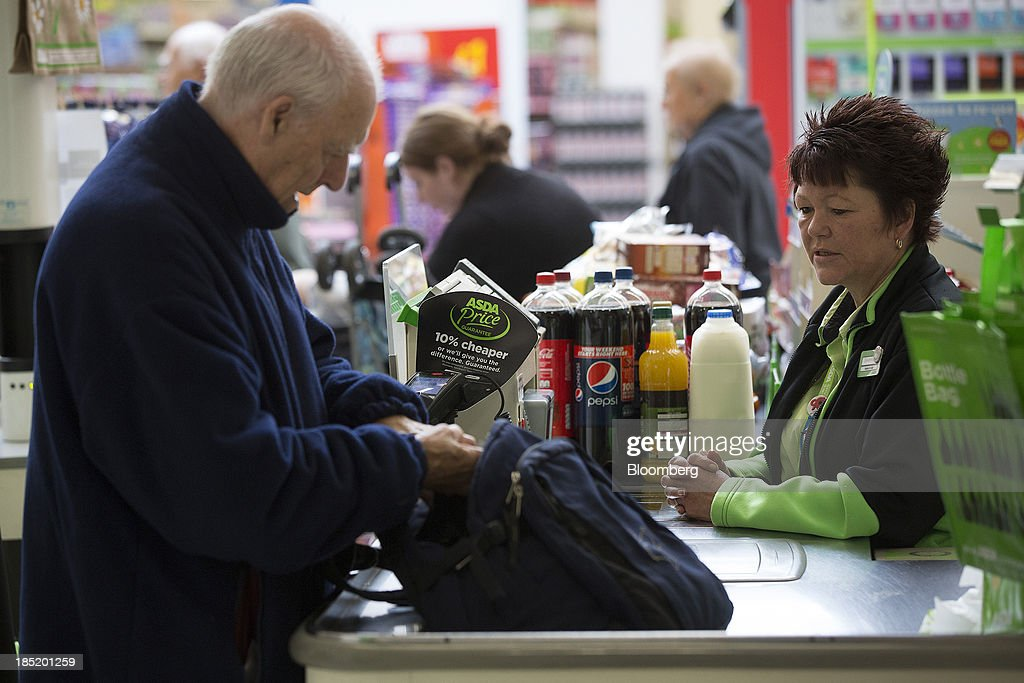 A customer, left pays for his shopping purchases at a check-out desk inside an Asda supermarket, the U.K. retail arm of Wal-Mart Stores Inc., in Watford, U.K., on Thursday, Oct. 17, 2013. U.K. retail sales rose more than economists forecast in September as an increase in furniture demand led a rebound from a slump the previous month. Photographer: Simon Dawson/Bloomberg via Getty Images
