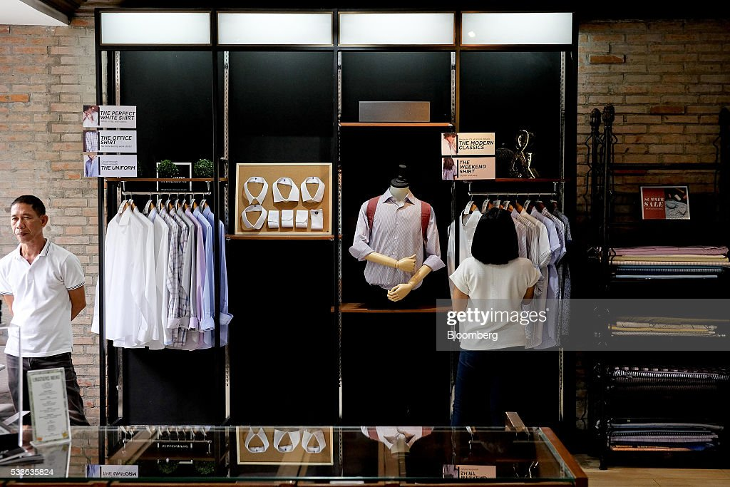 A customer left stands waiting at the Felipe Sons tailoring shop in Pasig City Metro Manila the Philippines on Friday May 20 2016 Gross domestic...
