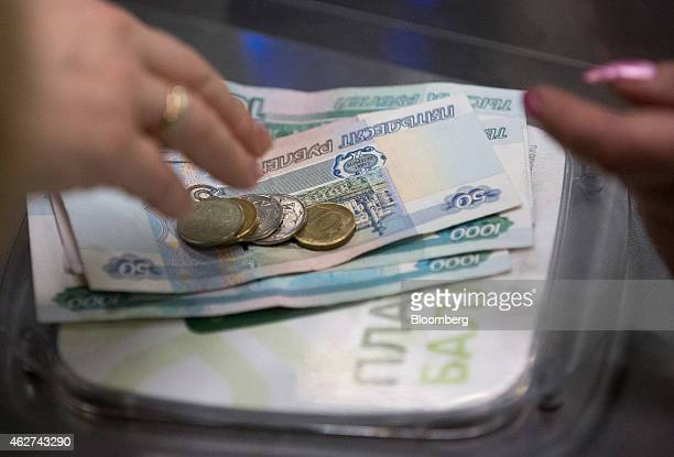 A customer left takes her ruble currency change at the checkout inside a Perekrestok supermarket operated by X5 Retail Group in Moscow Russia on...