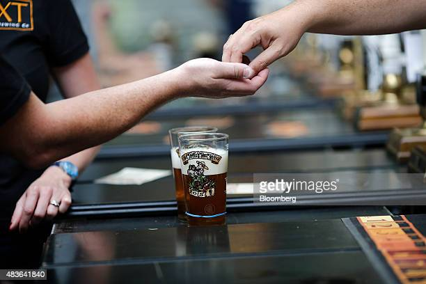 A customer left takes his change after paying for a pints of beer at the Great British Beer Festival in London UK on Tuesday Aug 11 2015 Europe has...