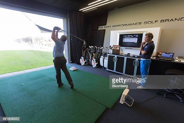 A customer left tees off on a golf driving range at the TaylorMade center of excellence operated by Adidas AG in Herzogenaurach Germany on Thursday...