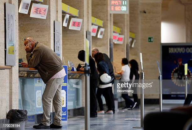 A customer left uses a mobile handset as he stands at a booths inside a Poste Italiane SpA post office in Rome Italy on Wednesday June 5 2013 Rome...