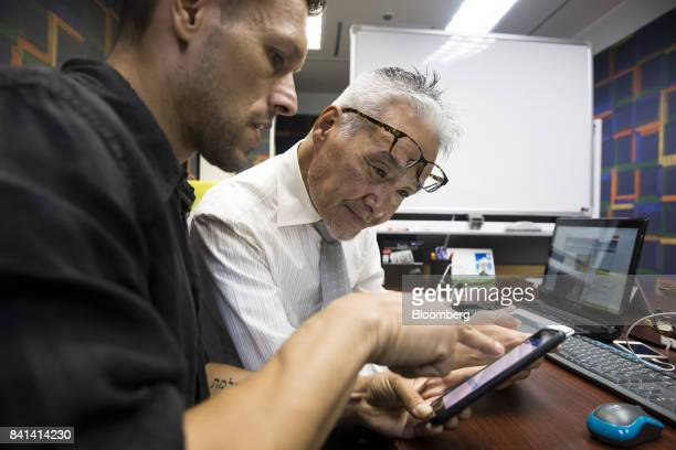 A customer left uses a smartphone as he sells bitcoin at the Coin Trader bitcoin retail store in Tokyo Japan on Wednesday Aug 30 2017 Stock of...