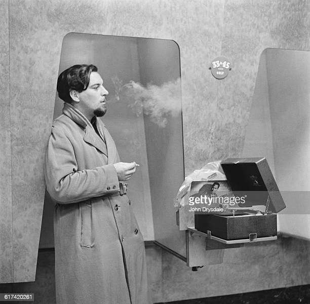 A customer listens to the latest record releases at a listening booth in the HMV shop at 363 Oxford Street London 24th November 1955 The records are...