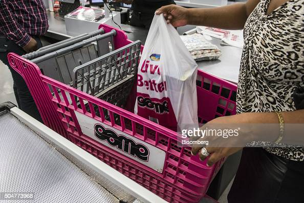 A customer loads a pink shopping cart with shopping bags at the check out counter of a Game supermarket operated by Massmart Holdings Ltd at the...