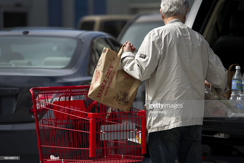A customer loads his car with Trader Joe's Co. shopping bags in San Francisco, California, U.S., on Friday, Sept. 13, 2013. Trader Joe's Co., the closely held grocery store chain, will end health benefits for part-time workers next year, directing them instead to anew insurance marketplaces as companies revamp medical coverage to fit the U.S. Affordable Care Act. Photographer: David Paul Morris/Bloomberg via Getty Images