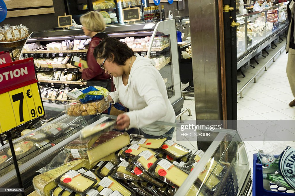 A customer look at cheeses in a Carrefour supermarket, on June 14, 2013 in Sainte-Geneviève-des-Bois, outside Paris. Installed in Sainte-Geneviève-des-Bois since fifty years, on June 15, 1963, this supermarket is the first of French giant retailer Carrefour group, but also the first in France.