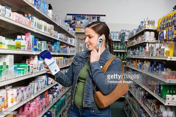 Customer looking at medication box and talking on cell phone