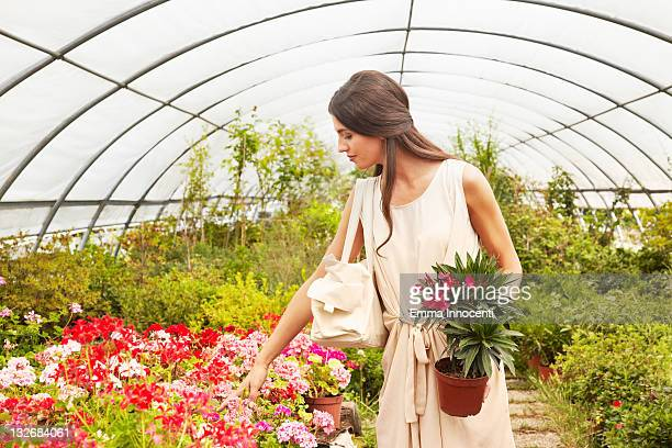 customer looking at pot flowers in garden centre