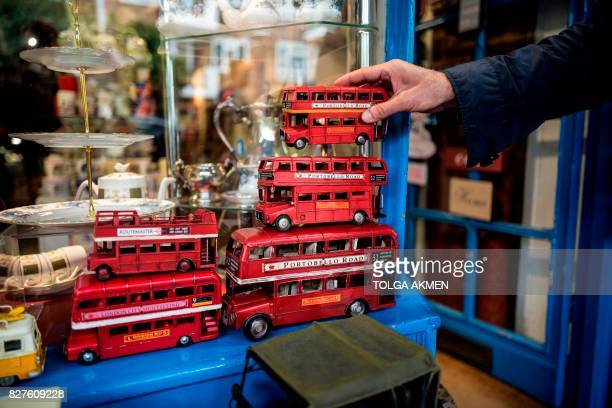 A customer looks a model of a red London Bus outside a shop on the Portobello Road Market in the Notting Hill district of west London on August 8...