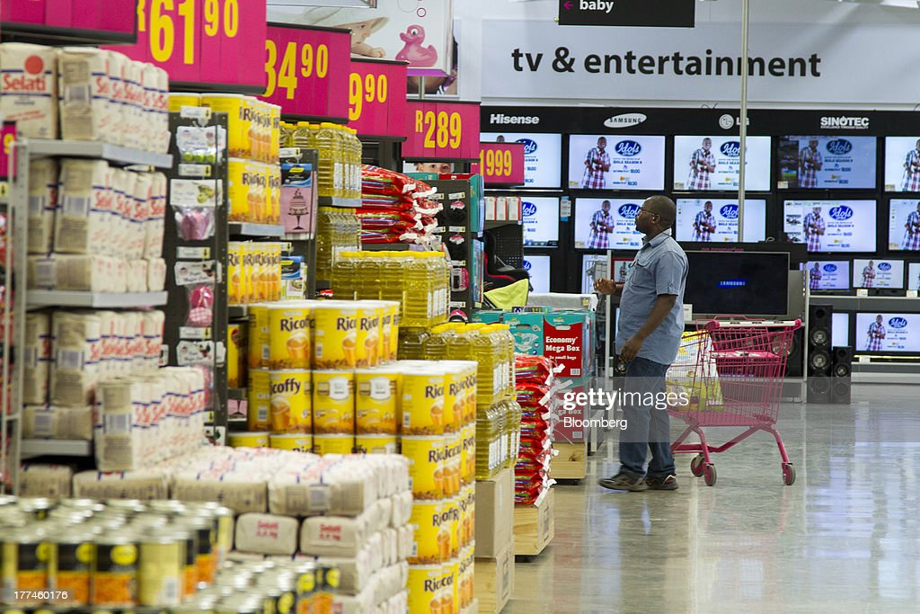 A customer looks along an aisle as he shops for food inside a Game supermarket, part of Massmart Holdings Ltd., in the Fourways district of Johannesburg, South Africa, on Thursday, Aug. 22, 2013. Massmart Holdings Ltd., the South African food and goods wholesaler owned by Wal-Mart Stores Inc., said revenue growth continued to slow in August after a downturn in consumer spending hurt first-half earnings. Photographer: Nadine Hutton/Bloomberg via Getty Images