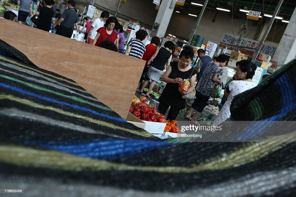 A customer looks at a bag of capsicum at Samsan Agricultural Wholesale Market in Incheon, South Korea, on Friday, Aug. 16, 2013. South Korean producer prices declined 0.9 percent in July from a year earlier after a 1.4 percent drop in June, the central bank said in a statement today. Photographer: SeongJoon Cho/Bloomberg via Getty Images