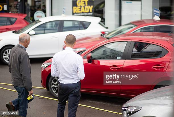 A customer looks at a brand new Mazda car that is offered for sale on the forecourt of a main motor car dealer in Brislington on October 6 2015 in...