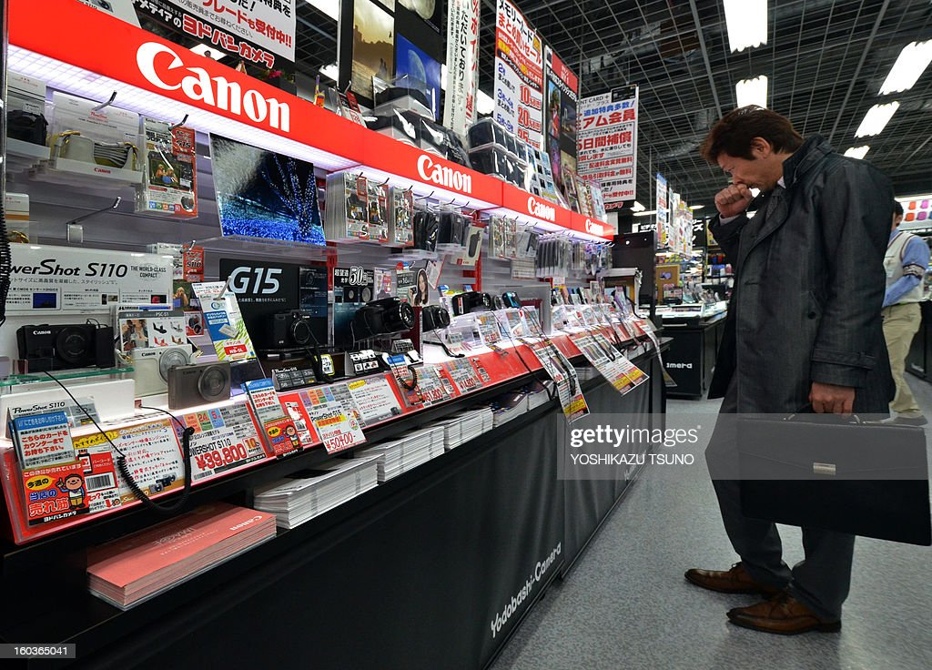 A customer looks at a Canon digital camera display in Tokyo on January 30, 2013. Canon said its full-year net profit fell 9.7 percent last year as it was hit by a slowdown in demand from debt-hit Europe and an export-sapping strong yen. AFP PHOTO / Yoshikazu TSUNO