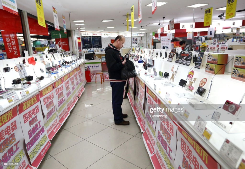 A customer looks at a digital camera at an electronics store in Beijing, China, on Wednesday, March 6, 2013. China maintained its economic-growth target at 7.5 percent for 2013 while setting a lower inflation goal of 3.5 percent, setting up a challenge for new leaders to keep prices in check without harming expansion. Photographer: Tomohiro Ohsumi/Bloomberg via Getty Images