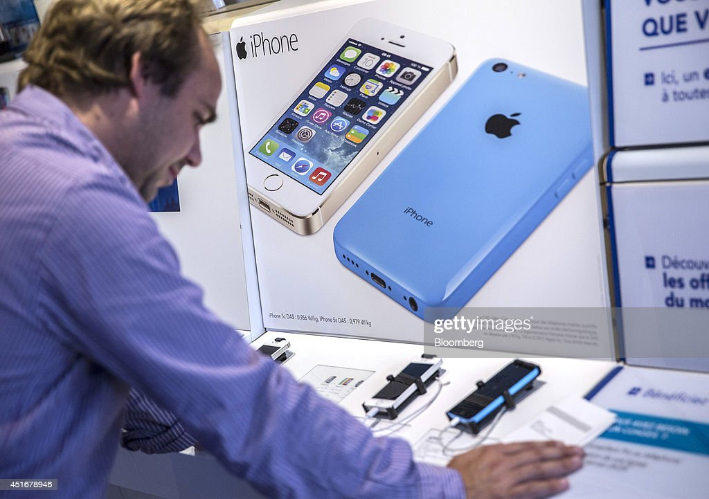 A customer looks at a display for the Apple Inc. iPhone 5c and iPhone 5s inside a Bouygues Telecom store, operated by Bouygues SA in Paris, France, on Thursday, July 3, 2014. Bouygues Telecom, France's third-largest mobile operator, was looking for a buyer as profitability and cash generation declined. Photographer: Balint Porneczi/Bloomberg via Getty Images