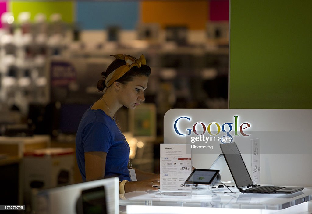 A customer looks at a display of Google Inc. Chrome laptops and Nexus 7 tablet devices inside Currys and PC World 2 in 1 store, operated by Dixons Retail Plc, at the Westfield Stratford City retail complex in London, U.K., on Thursday, Aug. 8, 2013. U.K. consumer confidence rose to the highest in more than three years as Britons' optimism about the economic outlook improved. Photographer: Simon Dawson/Bloomberg via Getty Images