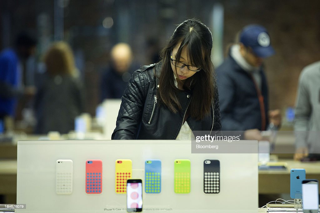 A customer looks at a display of iPhone 5C mobile devices as they stand on display inside Apple Inc.'s Covent Garden store in London, U.K., on Tuesday, Oct. 15, 2013. Burberry Group Plc named Christopher Bailey as chief executive officer to succeed Angela Ahrendts who will leave in 2014 to work as a senior vice president at Apple. Photographer: Simon Dawson/Bloomberg via Getty Images