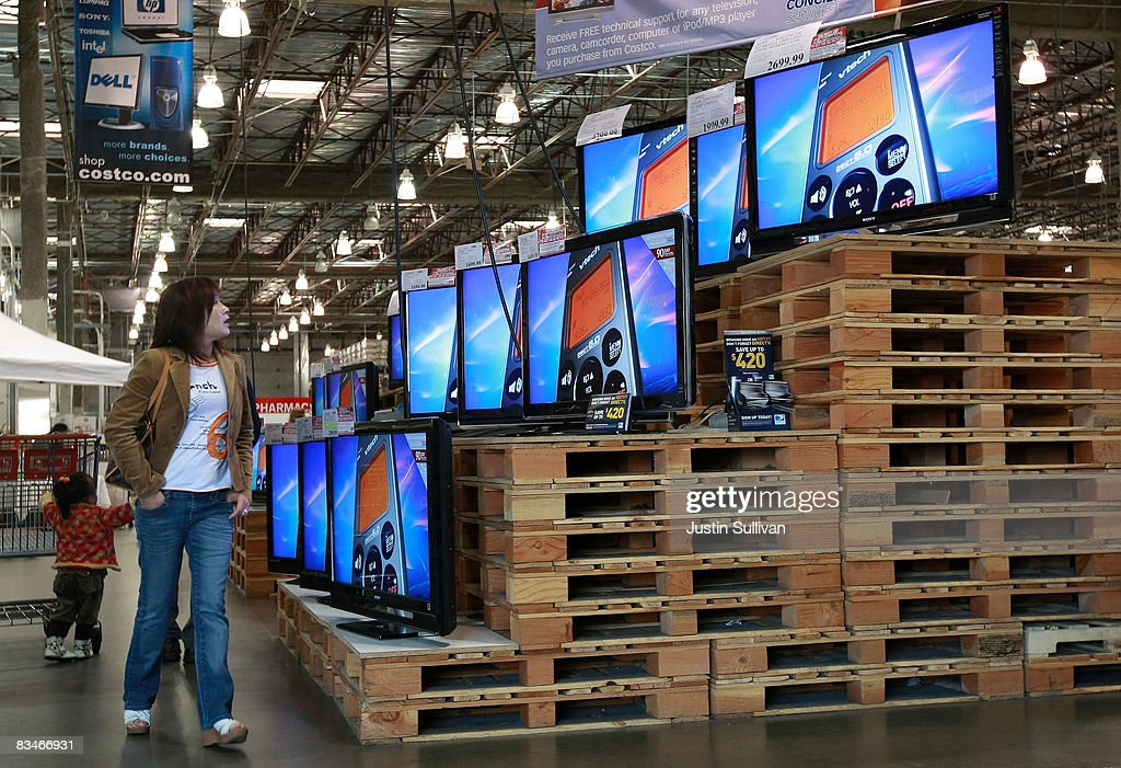 A customer looks at a display of televisions as she shops at a Costco store October 28 2008 in San Francisco California As the economy continues to...