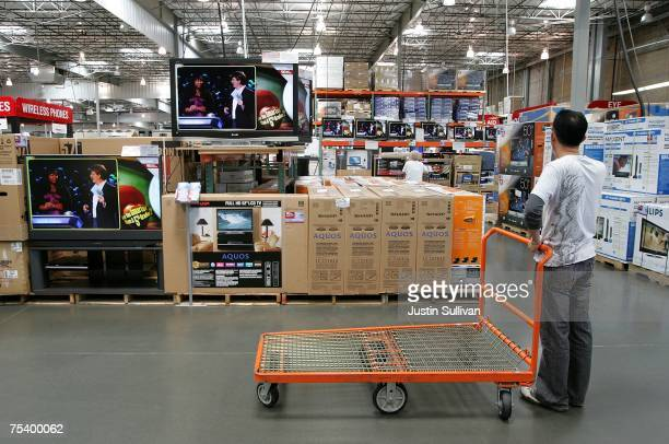 A customer looks at a display of televisions at a Costco warehouse store July 13 2007 in Richmond California Costco Wholesale Corporation reported a...