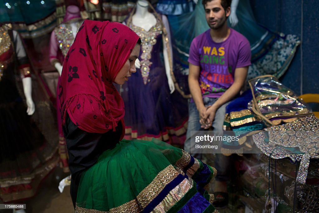 A customer looks at a dress made in India at a store inside Noor Shopping Center in Kabul, Afghanistan, Wednesday, Aug. 7, 2013. A smooth U.S. exit from Afghanistan will depend on Pakistans cooperation with the logistical pullout, as well as its backing for peace talks in neighboring Afghanistan and an end to any support for extremist proxies operating there. Photographer: Victor J. Blue/Bloomberg via Getty Images
