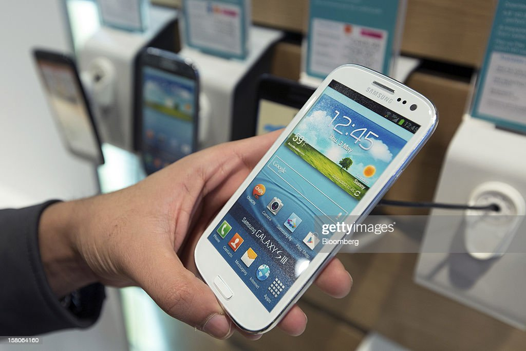 A customer looks at a Galaxy S III 4G-enabled handset, manufactured by Samsung Electronics Co., in this arranged photograph taken inside a EE (Everything Everywhere) store, a joint venture between France Telecom SA and Deutsche Telekom AG, in Stratford, U.K., on Monday, Dec. 5, 2012. France Telecom CEO Stephane Richard said in an interview last month that the Paris-based company has received interest from private-equity firms seeking a minority stake in the 50-50 venture, and may also consider an initial public offering of the unit. Photographer: Jason Alden/Bloomberg via Getty Images