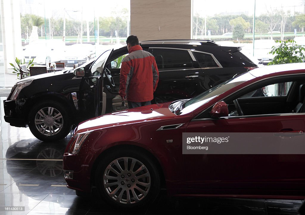 A customer looks at a General Motors Co. Cadillac SRX supports utility vehicle (SUV), while a Cadillac CTS vehicle is displayed at a dealership in Shanghai, China, on Friday, Feb. 8, 2013. China's services industries grew at the fastest pace since August as gains in retailing and construction aid government efforts to drive a recovery in the world's second-biggest economy. Photographer: Tomohiro Ohsumi/Bloomberg via Getty Images
