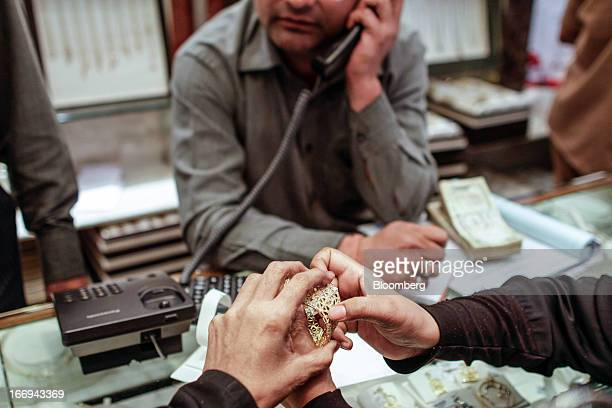 A customer looks at a gold bangle as a salesperson speaks on the telephone at the Dwarkadas Chandumal Jewellers store in the Zaveri Bazaar area of...