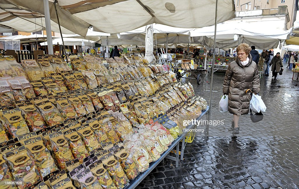 A customer looks at a goods displayed on a dried pasta stall at the Campo dei Fiori market in Rome, Italy, on Monday, Dec. 10, 2012. The imminent end of Prime Minister Mario Monti's government fueled the largest increase in Italian borrowing costs in four months and threatened to open a new front in Europe's crisis fight before a year-end summit. Photographer: Victor Sokolowicz/Bloomberg via Getty Images