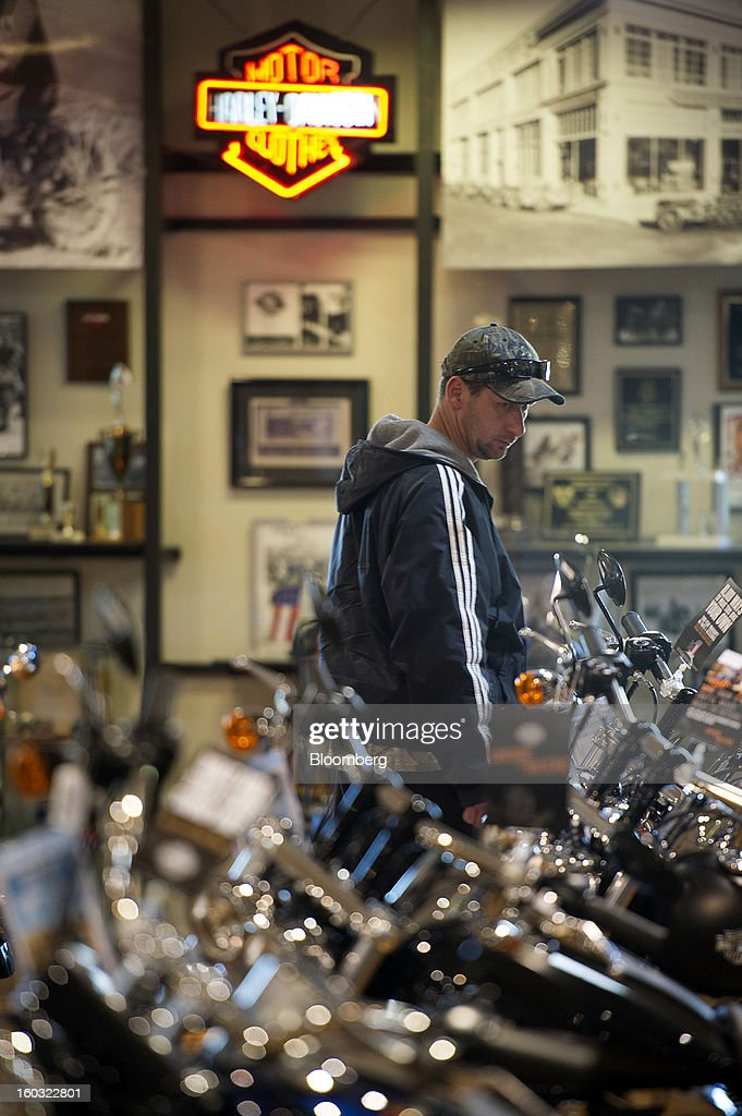 A customer looks at a Harley-Davidson Inc. motorcycle on the showroom floor at the Dudley Perkins Co. dealership in South San Francisco, California, U.S., on Monday, Jan. 28, 2013. Harley-Davidson reported fourth quarter revenue of $1.17 billion. Photographer: David Paul Morris/Bloomberg via Getty Images