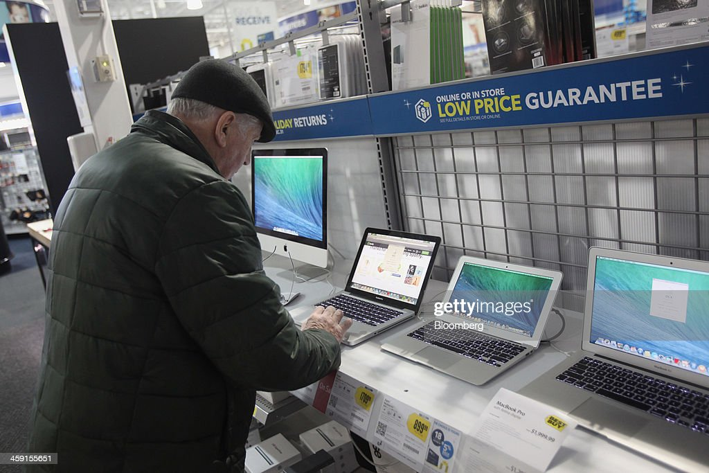 A customer looks at a laptop at a Best Buy Co. store in Northbrook, Illinois, U.S., on Monday, Dec. 23, 2013. U.S. shoppers flocked to stores during the last weekend before Christmas as retailers piled on steeper, profit-eating discounts to maximize sales in their most important season of the year. Photographer: Tim Boyle/Bloomberg via Getty Images