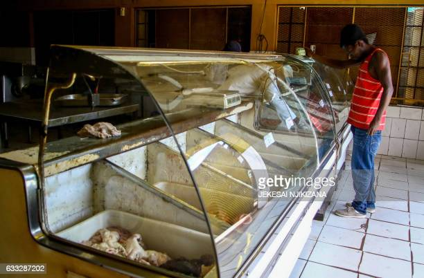 A customer looks at a meat refrigerator at a butchery in Mbare township in Harare on February 1 2017 Zimbabwe started levying a 15 percent valueadded...