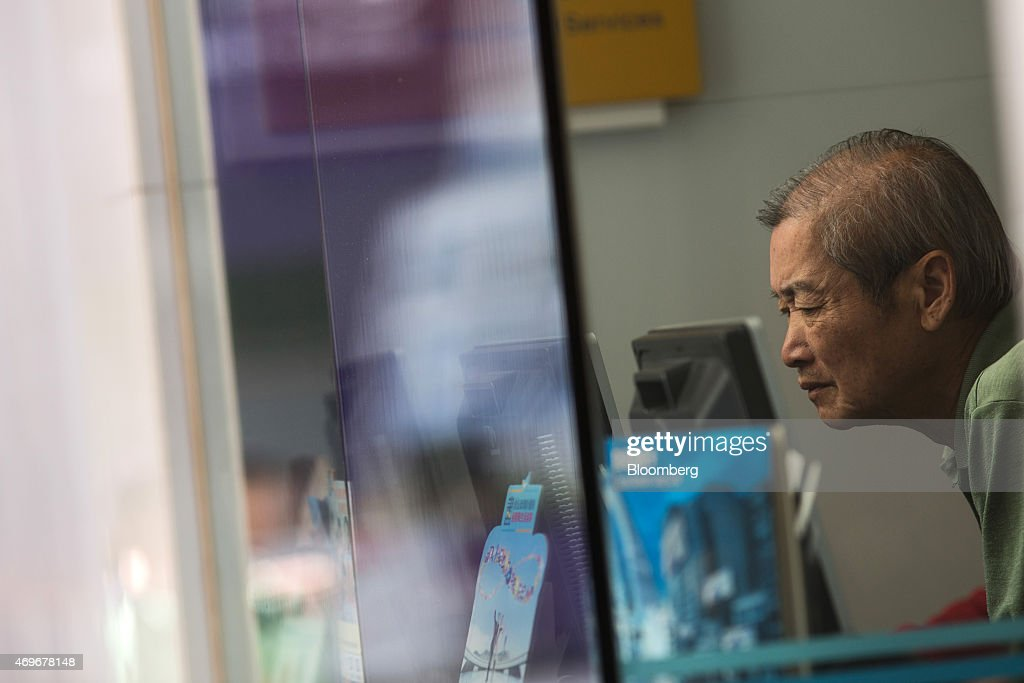 A customer looks at a monitor displaying stock prices at a China Construction Bank Corp branch in Hong Kong China on Tuesday April 14 2015 Chinese...