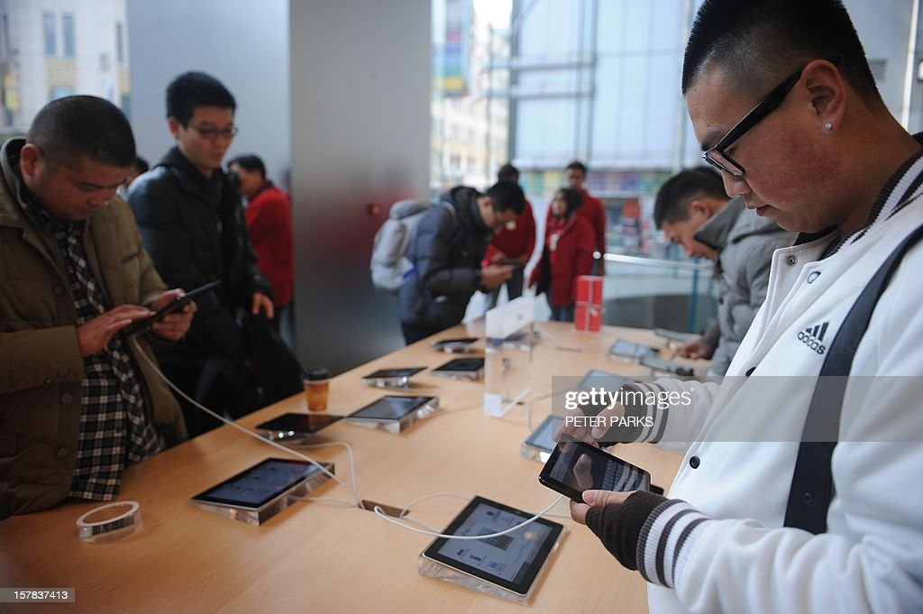 A customer looks at a new 'iPad mini' at an Apple store in Shanghai on December 7, 2012. The iPad mini and fourth generation iPad went on sale in China, with the iPhone 5 available here on December 14, Apple said in a recent statement. AFP PHOTO/Peter PARKS