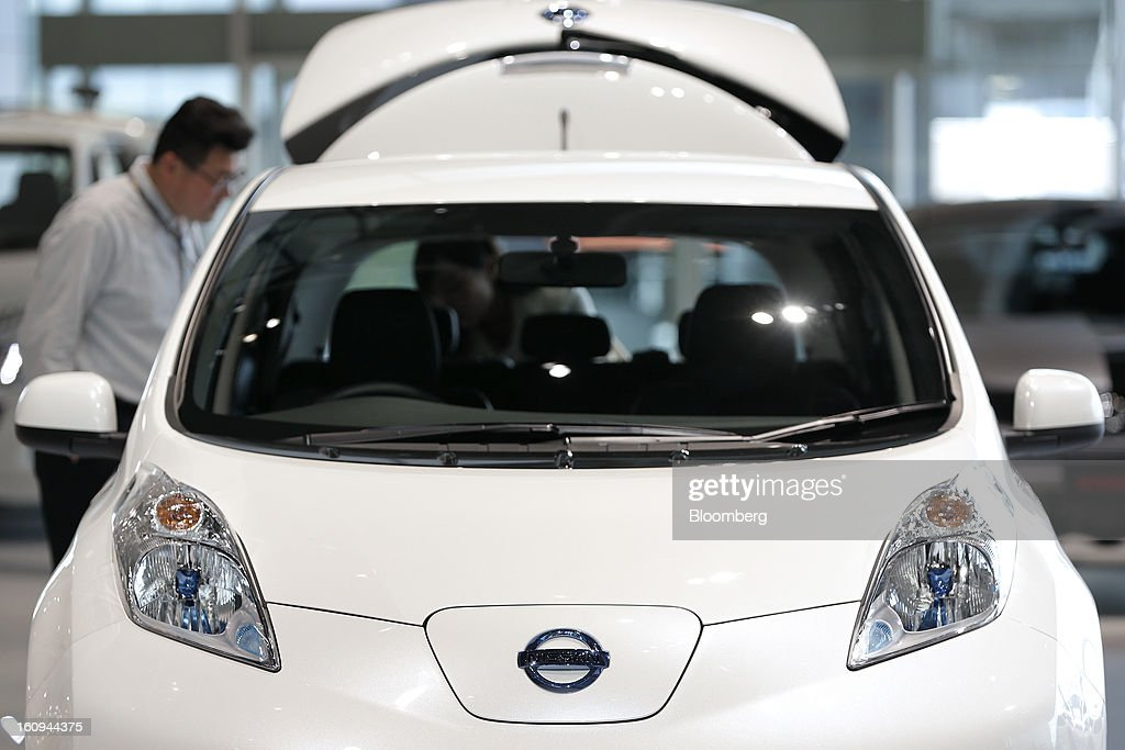 A customer looks at a Nissan Motor Co. Leaf electric vehicle (EV) displayed at the company's showroom in Yokohama, Kanagawa Prefecture, Japan, on Friday, Feb. 8, 2013. Nissan, Japan's second-biggest carmaker, reported third-quarter profit that fell short of analysts' estimates, after sales tumbled in China and new models trailed competitors in the U.S. Photographer: Kiyoshi Ota/Bloomberg via Getty Images