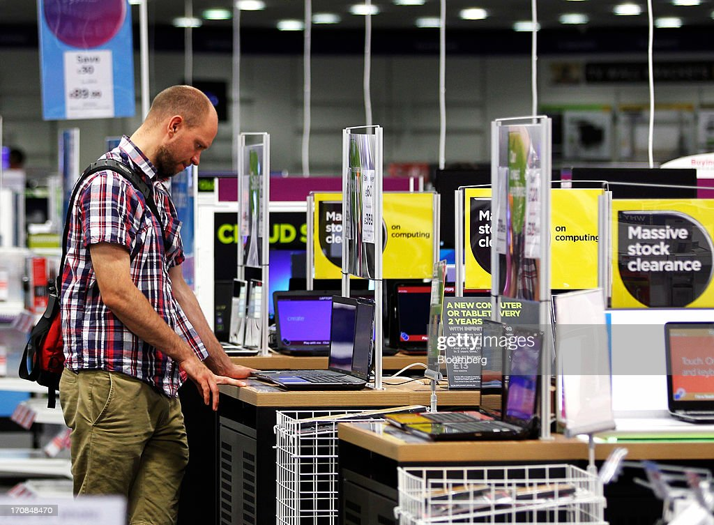 A customer looks at a PC laptop computer inside a Currys and PC World 2 in 1 store, operated by Dixons Retail Plc, in Manchester, U.K., on Tuesday, June 18, 2013. Dixons Retail Plc, the U.K.'s largest consumer-electronics retailer, said last month it will report annual pretax profit at the 'top end' of analysts' predictions after fourth-quarter revenue beat estimates on increased sales of tablets and services such as software tutorials. Photographer: Paul Thomas/Bloomberg via Getty Images