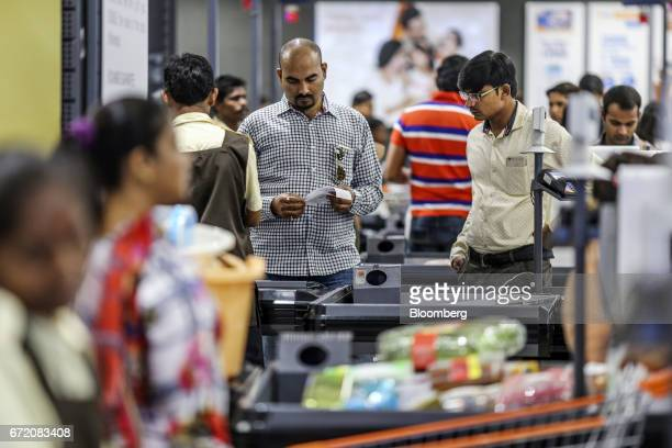 A customer looks at a receipt at a checkout counter of a Big Bazaar hypermarket operated by Future Retail Ltd in Mumbai India on Sunday April 16 2017...
