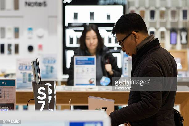 A customer looks at a Samsung Electronics Co Galaxy S7 Edge smartphone on display at the company's Dlight flagship store in Seoul South Korea on...