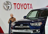 A customer looks at a vehicle from Japanese auto giant Toyota Motor at the company's showroom in Tokyo on January 27 2016 Toyota kept the title of...