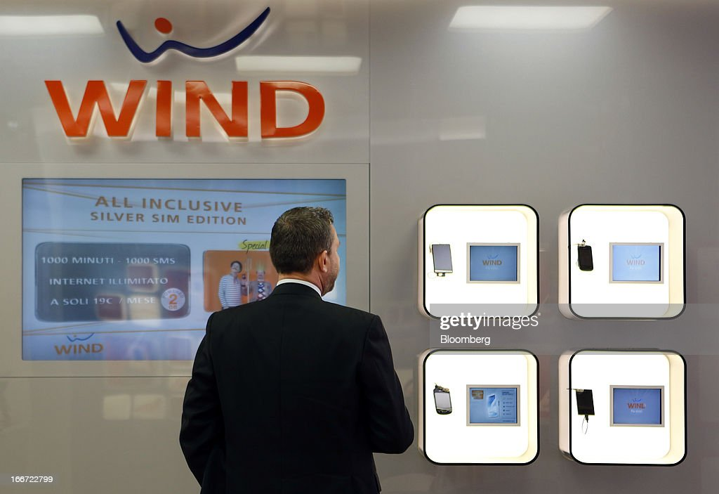 A customer looks at a wall display of smartphones inside a Wind SpA mobile phone store, owned by VimpelCom Ltd., in Rome, Italy, on Monday, April 15, 2013. Italy's state-owned postal service and Wind SpA, the country's third-largest mobile-phone company, are discussing a possible venture with Wind's fixed-line network Infostrada, Poste Italiane SpA Chief Executive Officer Massimo Sarmi said. Photographer: Alessia Pierdomenico/Bloomberg via Getty Images