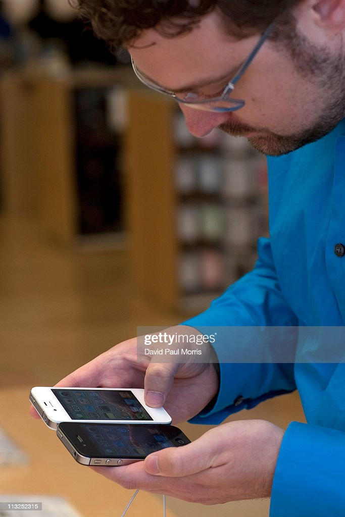 A customer looks at a white and a black iPhone 4 at the Apple store April 28, 2011 in Palo Alto, California. The long awaited white iPhone, first announced in June of 2010, went on sale worldwide for the first time today.