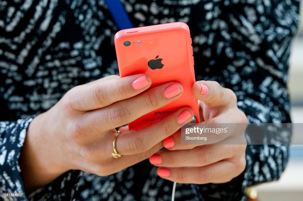 A customer looks at an Apple Inc. iPhone 5c device during the launch at the company's new store in Palo Alto, California, U.S., on Friday, Sept. 20, 2013. Apple Inc. attracted long lines of shoppers at its retail stores today for the global debut of its latest iPhones, in the company's biggest move this year to stoke new growth. Photographer: David Paul Morris/Bloomberg via Getty Images