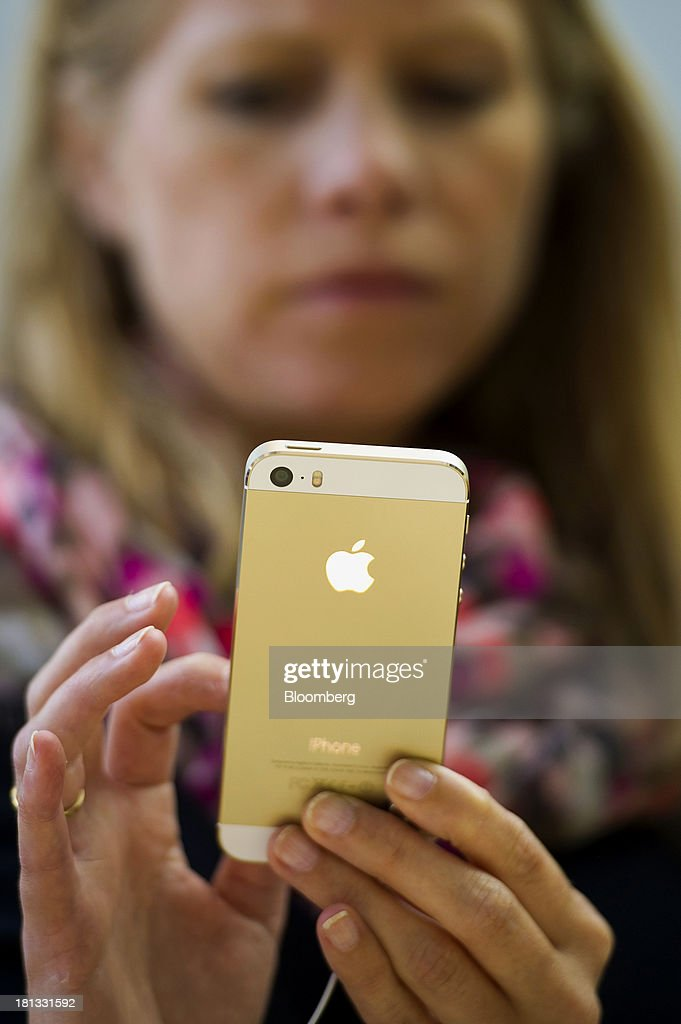 A customer looks at an Apple Inc. iPhone 5s device during the launch at the company's new store in Palo Alto, California, U.S., on Friday, Sept. 20, 2013. Apple Inc. attracted long lines of shoppers at its retail stores today for the global debut of its latest iPhones, in the company's biggest move this year to stoke new growth. Photographer: David Paul Morris/Bloomberg via Getty Images