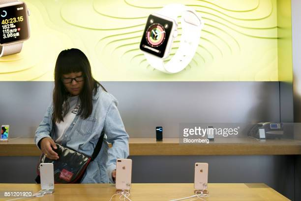A customer looks at an Apple Inc iPhone 8 Plus at the Apple Store at Sanlitun during the launch of the device in Beijing China on Friday Sept 22 2017...