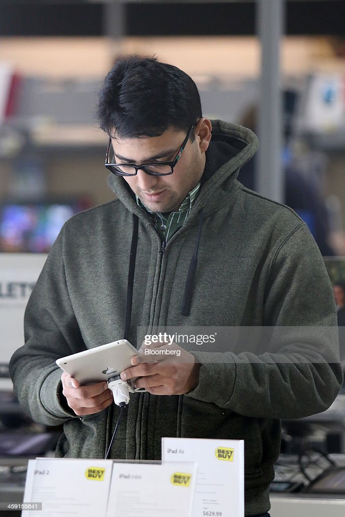 A customer looks at an Apple Inc. tablet at a Best Buy Co. store in Northbrook, Illinois, U.S., on Monday, Dec. 23, 2013. U.S. shoppers flocked to stores during the last weekend before Christmas as retailers piled on steeper, profit-eating discounts to maximize sales in their most important season of the year. Photographer: Tim Boyle/Bloomberg via Getty Images